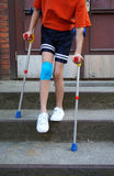 Little girl with crutches at the stair. Stock Photos