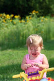 Little Girl Crying. An unhappy little girl sits crying on her toy ATV (All Terrain Vehicle Stock Photography