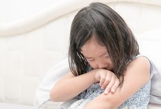 Little girl crying on bed, sad and angry. Concept royalty free stock photography