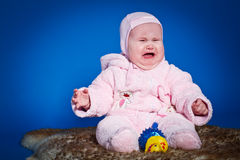 Little girl crying. On a blue background Royalty Free Stock Photography