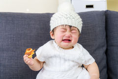Little girl crying with bread holding on hand Royalty Free Stock Image