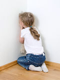 Little girl crying in the corner. Royalty Free Stock Image