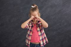 Little girl crying and covering eyes with hands royalty free stock images