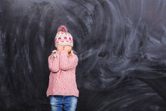 Little girl crying. Cute little girl on a gray background in a pink sweater Royalty Free Stock Images