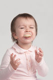 Little girl crying eating cookies Royalty Free Stock Images