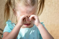 A little girl is crying and rubbing her eyes with her hands. Children`s hysteria. royalty free stock photography