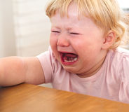 Little girl crying. Crying little girl sitting at the table royalty free stock photography