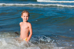 Little girl crying in the spray of waves at sea. On a sunny day Royalty Free Stock Photography