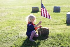 Free Little Girl Cub Scout Placing American Flag On Veterans Grave On Memorial Day Stock Image - 184254681