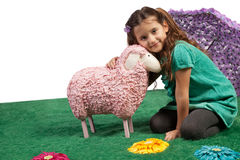 Little girl cudddling a toy sheep. Cute pretty little girl sitting on the floor on an artificial meadow cudddling a large pink woolly toy sheep with a lovely royalty free stock photo