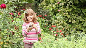 Little girl cuddle kitten. In the garden stock footage