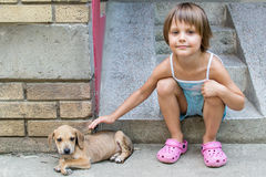 Little girl cuddle a puppy Stock Photo