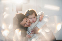 Little girl cuddling with her mother in a nice winter clothes, baby, lifestyle, childhood, joy, family values, life style Royalty Free Stock Photography