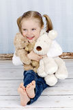 Little girl cuddling with plush toys Stock Photos