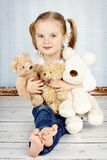 Little girl cuddling with plush toys Stock Images
