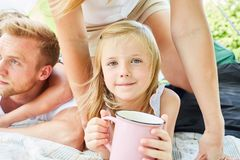 Little girl with a cup while camping. In front of the tent in the summer holidays stock images
