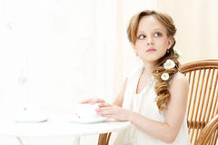 Little girl with cup of tea. Beautiful little girl sitting in cafe and drinking tea Royalty Free Stock Photo