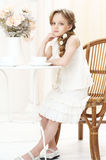 Little girl with cup of tea. Beautiful little girl sitting in cafe and drinking tea Stock Photo