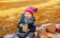 Little girl with cup of tea sitting Stock Photos