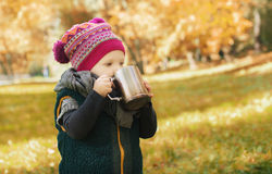 Little girl with cup of tea standing in the autumn forest Royalty Free Stock Photography