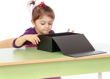 Little girl curiously looking at the big black box Royalty Free Stock Image