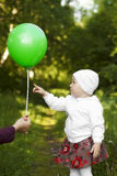 Little girl curiously shows a balloon Royalty Free Stock Images