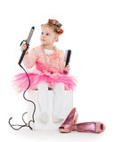 Little girl with curling iron. Stock Images