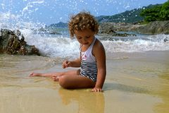 Little girl with curls on the beach against the background of splashes from the wave. Sandy beach. Child on the beach. Sea wave Royalty Free Stock Photos