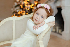 Little girl Curly baby sitting in a chair and sad at Christmas Royalty Free Stock Photos