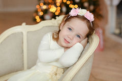 Little girl Curly baby sitting in a chair and smiling at Christm Royalty Free Stock Images