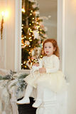 Little girl Curly baby sitting on the mantel at Christmas Stock Photos