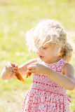 A little girl with curly blond hair holds two cooked crayfish in her hands Royalty Free Stock Images