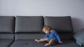Little girl with curly blond hair jumps on sofa. Blue clothes. Feels happy. Slow motion. Little girl with curly blond hair jumps on sofa. Blue clothes. Feels stock video footage
