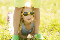 Little girl with curly blond hair in sunglasses lies on the grass. Little girl with curly blond hair in sunglasses lies on grass Royalty Free Stock Photography