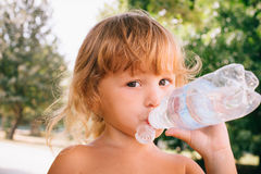The little girl with curly golden hair pleasure drinks water fro Royalty Free Stock Images