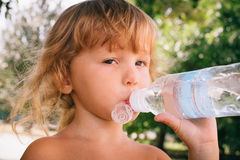 The little girl with curly golden hair pleasure drinks water fro Royalty Free Stock Photos
