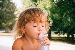 The little girl with curly golden hair pleasure drinks water fro Royalty Free Stock Photo