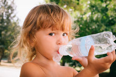 The little girl with curly golden hair pleasure drinks water fro. The little girl with pleasure drink water outdoors. A child is drinking clean water from a Royalty Free Stock Photo