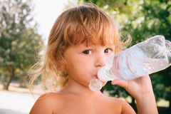 The little girl with curly golden hair pleasure drinks water fro. The little girl with pleasure drink water outdoors. A child is drinking clean water from a stock image