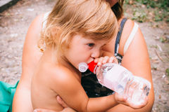 The little girl with curly golden hair pleasure drinks water fro. The little girl with pleasure drink water outdoors. A child is drinking clean water from a Stock Photo
