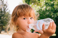 The little girl with curly golden hair pleasure drinks water fro. The little girl with pleasure drink water outdoors. A child is drinking clean water from a Stock Images
