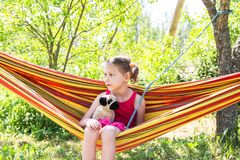 Adorable little girl with curly hair in colorful striped hammock on summer nature background in countryside royalty free stock images