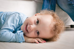 Little girl with curly hair winks. Child lying on a sofa. Portr royalty free stock photo