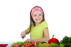 Little girl cut fresh tomatoes. Royalty Free Stock Images