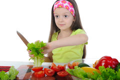 Little girl cut salad at the table Stock Images