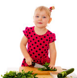 Little girl cut vegetables royalty free stock photography
