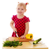 Little girl cut vegetables Stock Photography