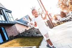 Cute little girl wearing crown and holding magic wand walking in the street royalty free stock images