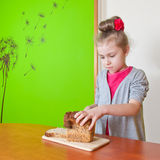 Little girl cuts the bread Royalty Free Stock Images