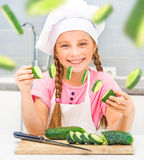 Little girl cuts cucumbers Royalty Free Stock Images